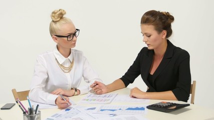 Two businesswomen working together at desk office.