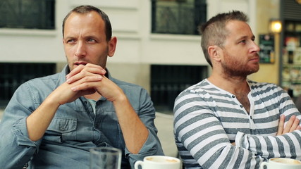 Unhappy, conflicted male friends in cafe in the city