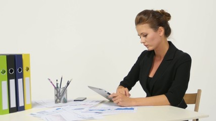 Businesswoman wearing casual shirt sitting at desk and looking