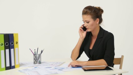 Laughing businesswoman on the phone at her desk in bright office