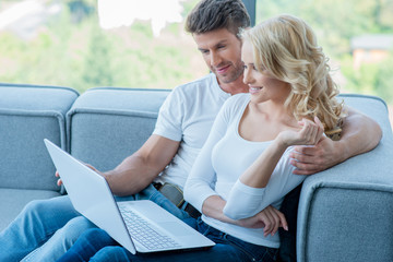 Couple relaxing on a sofa using laptop