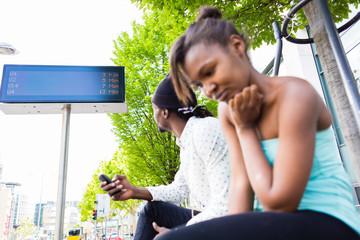 Afrikanisches Pärchen warten an Bushaltestelle