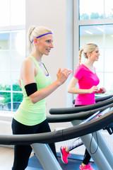 Frauen im Fitness Studio auf Laufband beim Sport