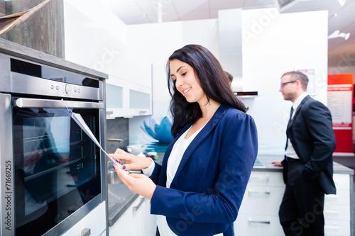 Leinwanddruck Bild Paar sucht Küche im Möbelhaus aus