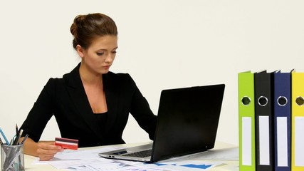 Smiling businesswoman doing online shopping through laptop and