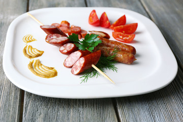 Assortment of tasty thin sausages on plate, on wooden