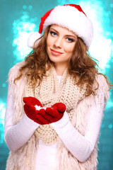 Portrait of woman in scarf and gloves on bright blue background