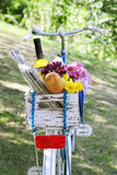 Bicycle with flowers, bread and bottle of wine in wooden box