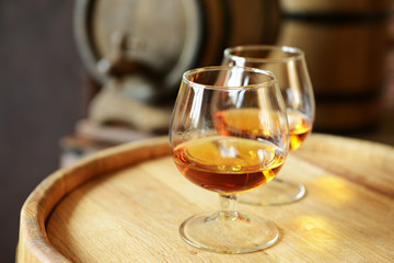 Glasses of brandy in cellar with old barrels