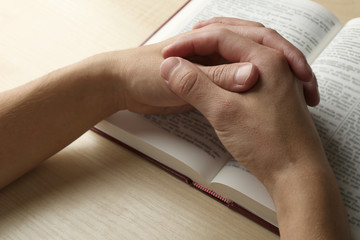 Male hands with Bible on wooden table