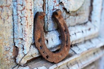 Old horse shoe on vintage wooden door, outdoors