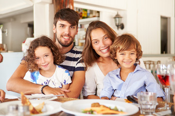 Portrait Of Family Enjoying Meal In Restaurant