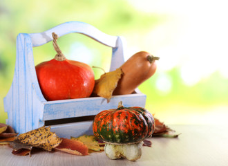 Pumpkins in wooden box and leaves on table on natural