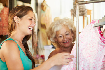 Sales Assistant Showing Senior Female Customer Clothes