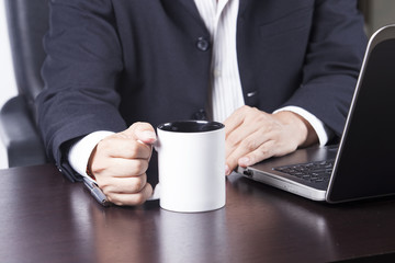hand of Businessman holding cup of coffee