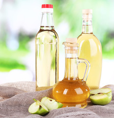 Apple cider vinegar in glass bottles and ripe fresh apples,