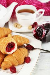 Breakfast with tea, apple juice, jam and fresh croissants