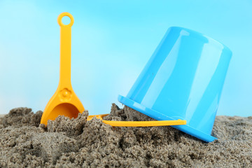 Spade and bucket  on sandy beach background