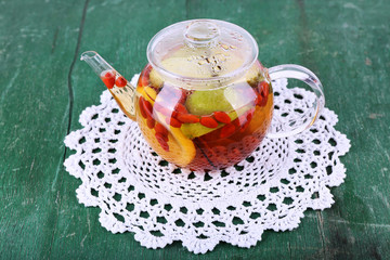 Fruit drink in teapot on lace napkin on green wooden background