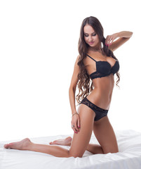 Exciting lingerie model posing on silk sheets