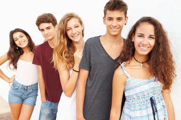 Portrait Of Teenage Group Leaning Against Wall