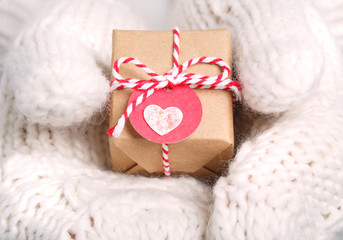 Little handmade gift box in hands with gloves