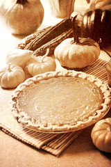 Pumpkin pie with autumn pumpkins and corn