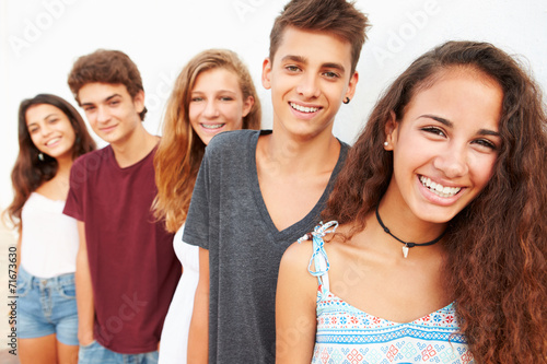 Portrait Of Teenage Group Leaning Against Wall - 71673630