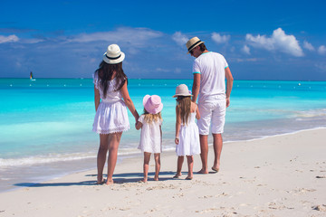 Back view of young beautiful family during tropical beach