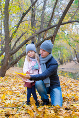 Little girl and dad in autumn park outdoors