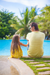 Little girl with father have fun near swimming pool at exotic
