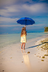 Little cute girl with blue umbrella walking on tropical beach