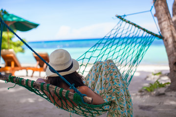 Young woman lying in the hammock on tropical beach