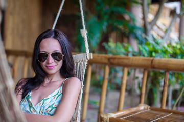 Beautiful brunette woman in long dress relaxing in hammock