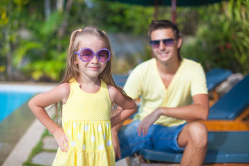 Cute girl with her young dad near swimming pool