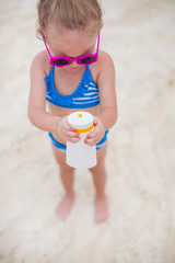 Little cute adorable girl in swimsuit rubs sunscreen herself