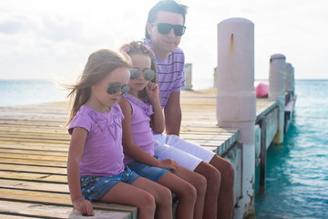 Family of three sitting on wooden dock enjoying ocean view