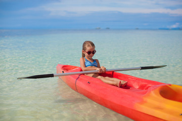 Little adorable girl kayaking in clear blue sea