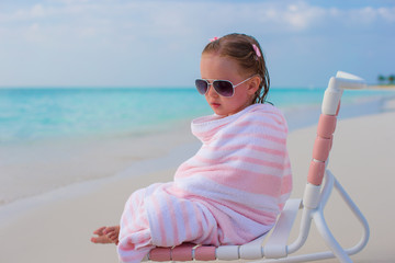 Adorable little girl covered with towel sitting on beach chair