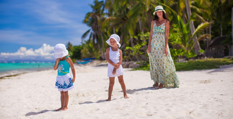 Young mother with her adorable daughters during beach vacation