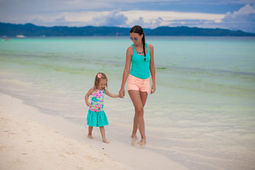 Young mom and her little daughter walking by the sea