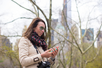 Young girl with a phone in the park
