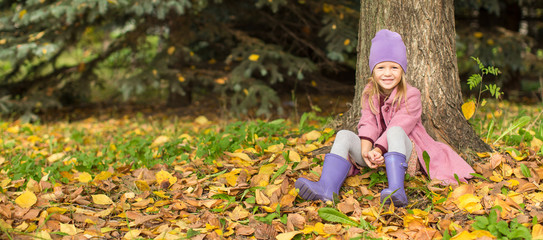 Little happy girl in autumn park outdoors