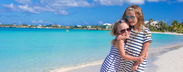 Two little adorable girls enjoy tropical beach vacation