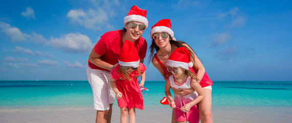 Happy family of four in Christmas Hats on white beach