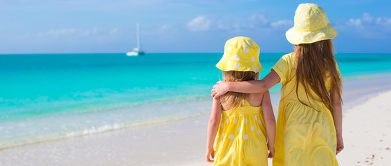 Back view of two little girls during tropical beach