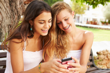 Two Teenage Girls Using Mobile Phone Sitting On Park Bench