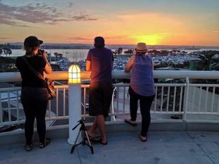 A Photographer Photographs the Sunset over Boat Marina