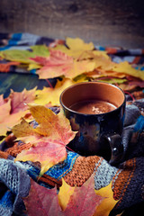 Cup of coffee set with autumn leaves and a warm scarf
