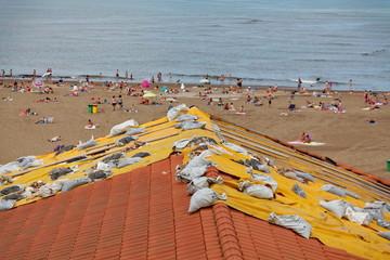 Bâche sur un toit maintenue par des sacs de sable.